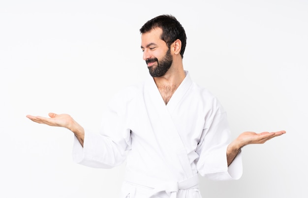 Jonge mens die karate over geïsoleerde witte holding copyspace met twee handen doet