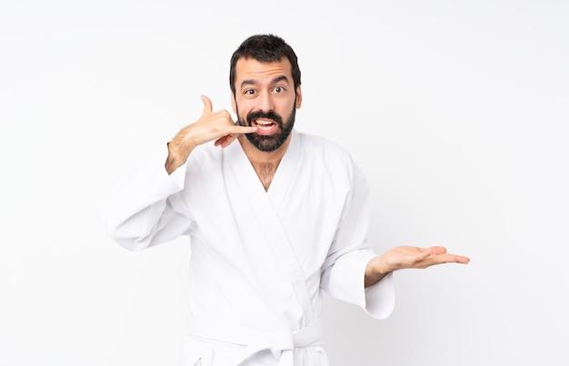 Jonge mens die karate over geïsoleerde witte muur doet die telefoongebaar en het twijfelen maakt