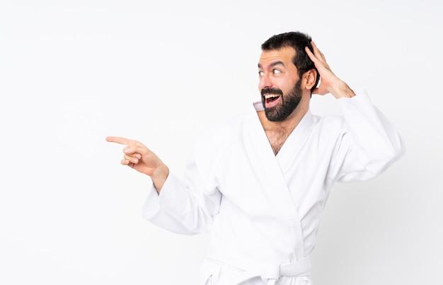 Jonge mens die karate over geïsoleerde witte muur doet verrast en vinger aan de kant richt