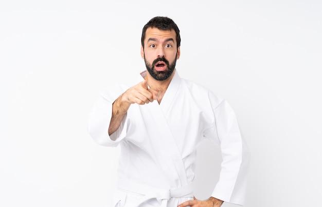 Jonge mens die karate over geïsoleerde witte muur doet verrast en voorzijde richt