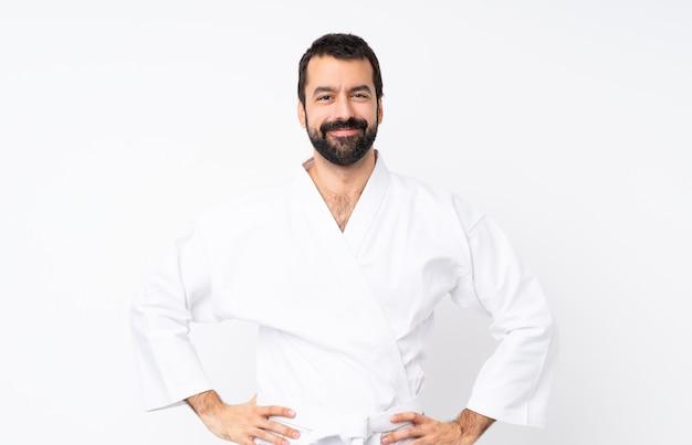 Jonge mens die karate over het geïsoleerde witte stellen met wapens bij heup en het glimlachen doet