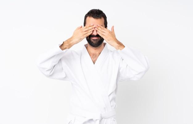 Jonge mens die karate over wit doet dat ogen behandelt door handen