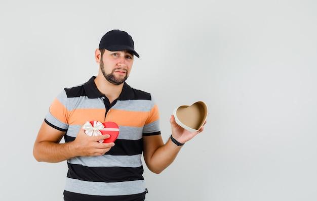 Jonge mens die lege huidige doos in t-shirt, glb toont en teleurgesteld kijkt.