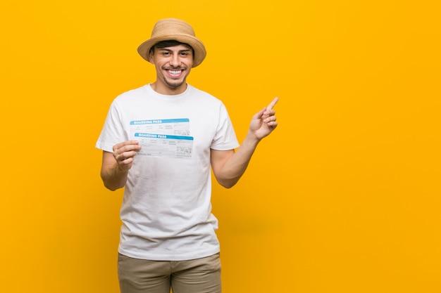 Jonge mens die luchtkaartjes houden glimlachend vrolijk wijzend met weg wijsvinger