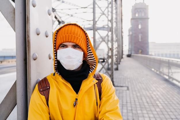 Jonge mens die medisch beschermend masker, oranje glb en geel windjack draagt dat met zorg kijkt, denkend aan pandemisch coronavirus, die zich op de brug in een lege stad bevindt. covid-19 virusconcept.