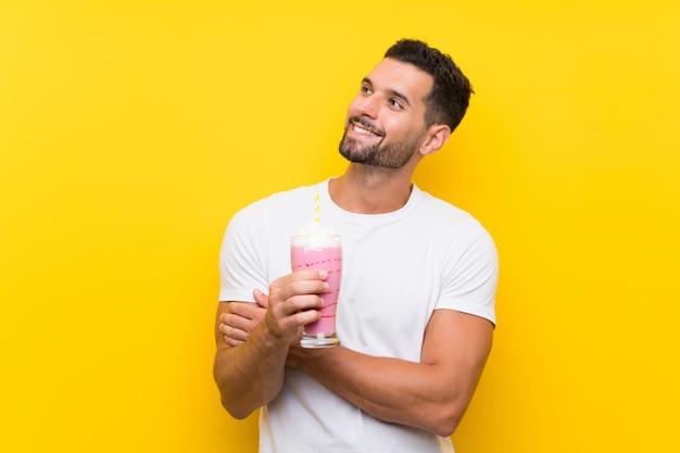 Jonge mens die met aardbeimilkshake over geïsoleerde gele muur omhoog terwijl het glimlachen kijkt