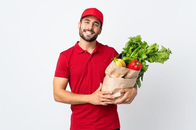 Jonge mens die met baard een zakhoogtepunt van groenten houdt dat bij het witte muur toejuichen wordt geïsoleerd