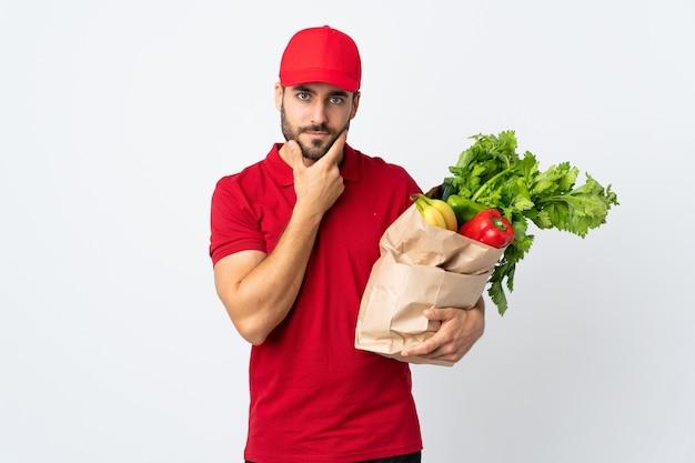 Jonge mens die met baard een zakhoogtepunt van groenten houdt dat op wit wordt geïsoleerd denkend een idee