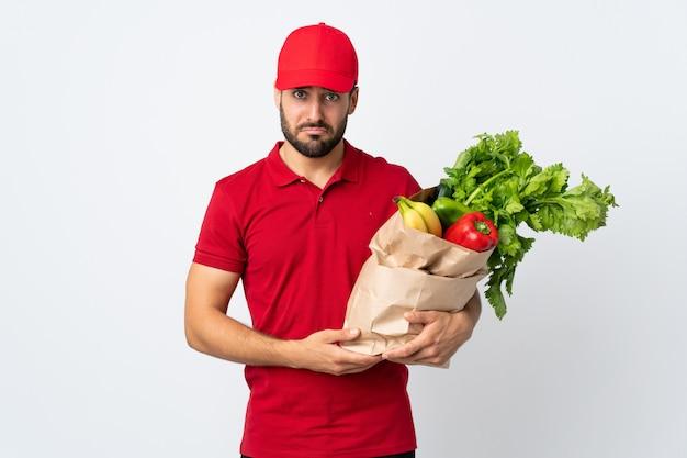 Jonge mens die met baard een zakhoogtepunt van groenten houdt dat op witte droevige muur wordt geïsoleerd