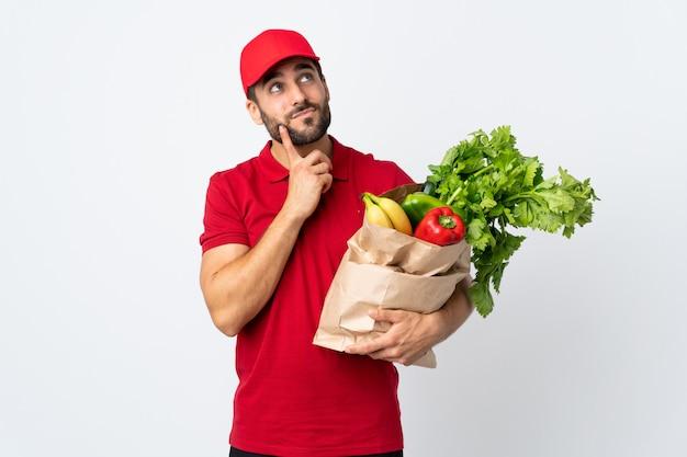 Jonge mens die met baard een zakhoogtepunt van groenten houdt die op witte muur wordt geïsoleerd denkend een idee