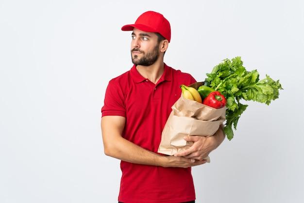 Jonge mens die met baard een zakhoogtepunt van groenten houdt die op witte muur wordt geïsoleerd kijkend kant