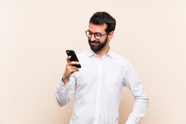 Jonge mens die met baard mobiel met glazen en het glimlachen houdt
