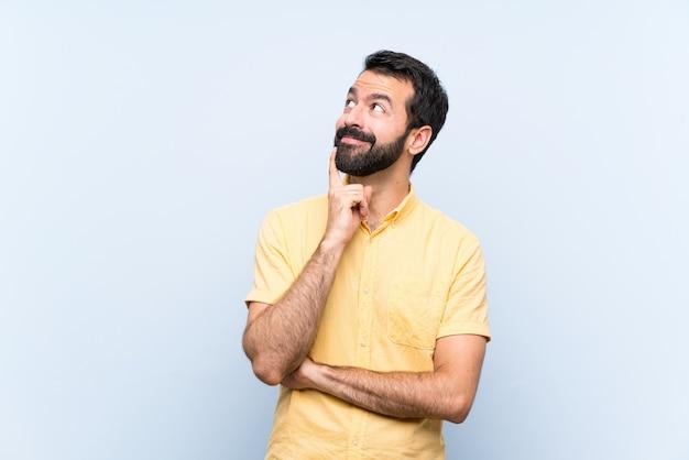 Jonge mens die met baard over geïsoleerde blauwe muur een idee denken terwijl omhoog het kijken