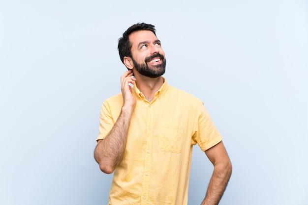 Jonge mens die met baard over geïsoleerde blauwe muur een idee denkt