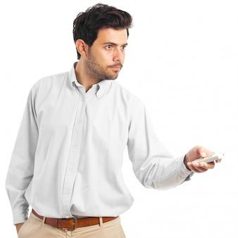 Jonge mens die met een afstandsbediening op een witte achtergrond richt
