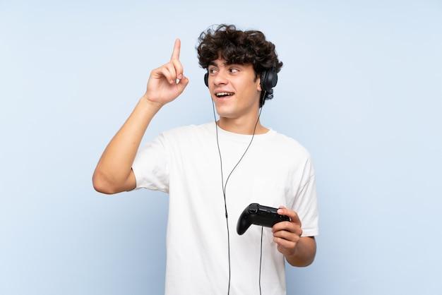 Jonge mens die met een videospelletjecontrolemechanisme over geïsoleerde blauwe muur speelt die de oplossing van plan is te realiseren terwijl het opheffen van een vinger