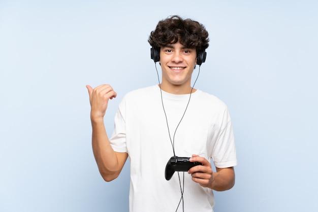 Jonge mens die met een videospelletjecontrolemechanisme speelt over geïsoleerde blauwe muur die aan de kant richten om een product te presenteren
