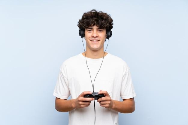 Jonge mens die met een videospelletjecontrolemechanisme speelt over geïsoleerde blauwe muur die heel wat glimlacht