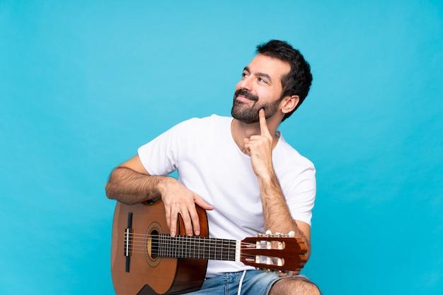 Jonge mens die met gitaar over geïsoleerd blauw een idee denkt terwijl omhoog het kijken