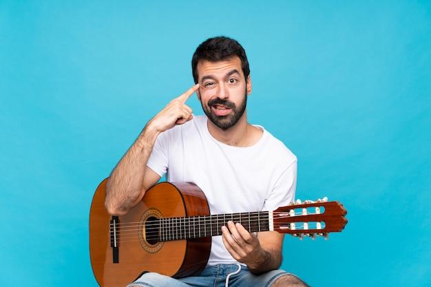 Jonge mens die met gitaar over geïsoleerde blauwe achtergrond het gebaar van waanzin maakt die vinger op het hoofd zet