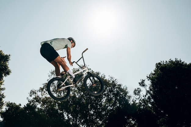 Jonge mens die met omhoog hoge fiets springt
