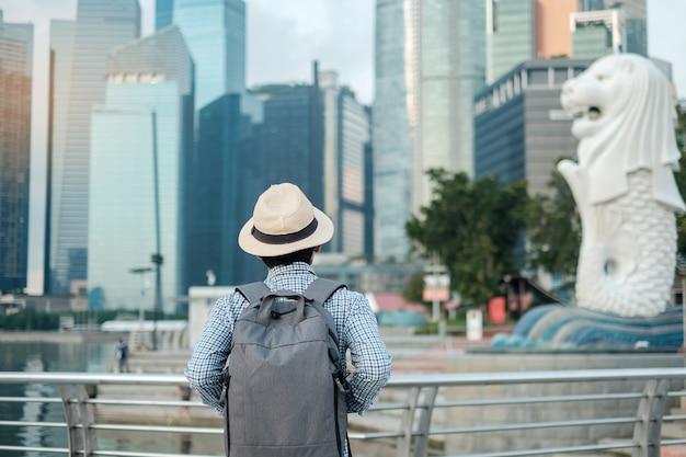 Jonge mens die met rugzak en hoed in de ochtend reizen, solo aziatisch reizigersbezoek in stad de van de binnenstad van singapore. oriëntatiepunt en populair voor toeristenaantrekkelijkheden. azië reizen concept