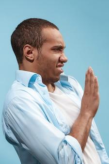 Jonge mens die met weerzinwekkende uitdrukking iets afstoot, dat op het blauw wordt geïsoleerd