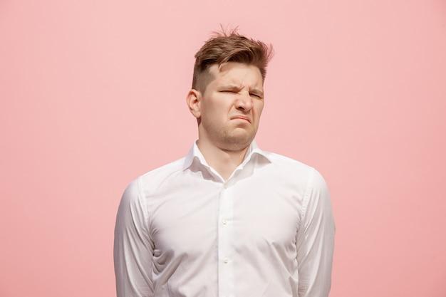Jonge mens die met weerzinwekkende uitdrukking iets afstoot, geïsoleerd op het roze