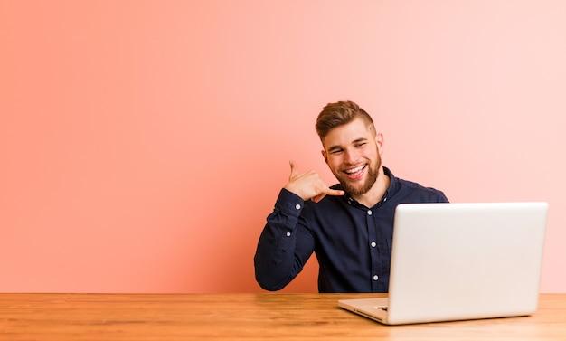 Jonge mens die met zijn laptop werkt die een mobiel telefoongesprekgebaar met vingers toont.