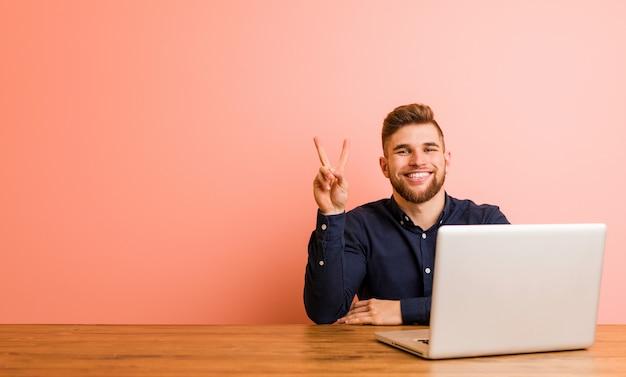 Jonge mens die met zijn laptop werkt die nummer twee met vingers toont.
