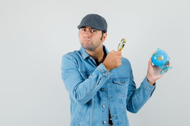 Jonge mens die minibol met vergrootglas in jasje, glb kijkt en verbaasd kijkt.