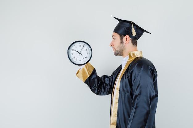 Jonge mens die muurklok in gediplomeerd uniform bekijkt en gefocust kijkt.