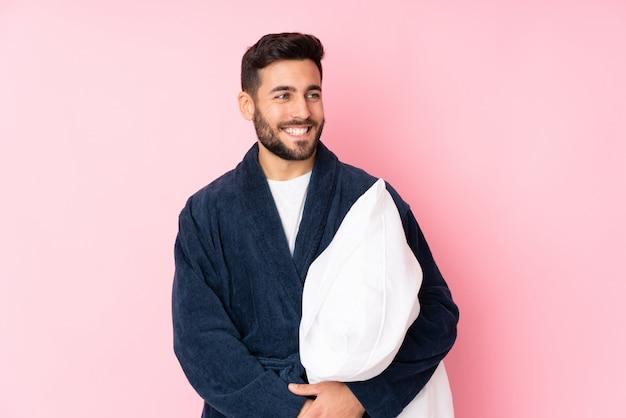 Jonge mens die naar slaap gaat geïsoleerd bij het roze muur lachen