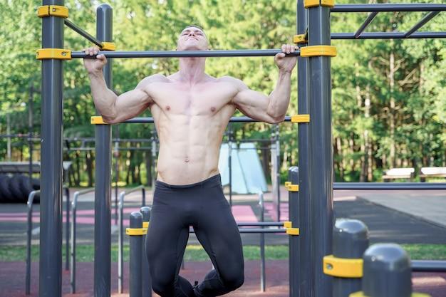 Jonge mens die oefening op een rekstok in openlucht doet