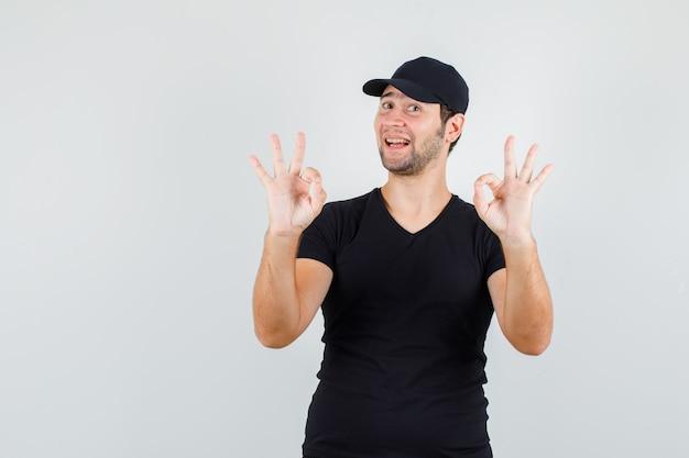 Jonge mens die ok teken in zwart t-shirt toont