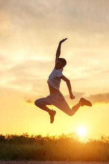 Jonge mens die omhoog tegen de zonsonderganghemel springt