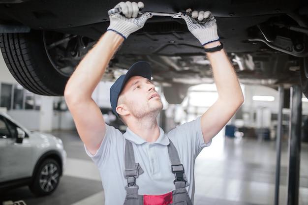 Jonge mens die onder auto werkt. hij kijkt naar rechts en houdt met beide handen een grote sleutel vast. hij is geconcentreerd. man werkt in garage.