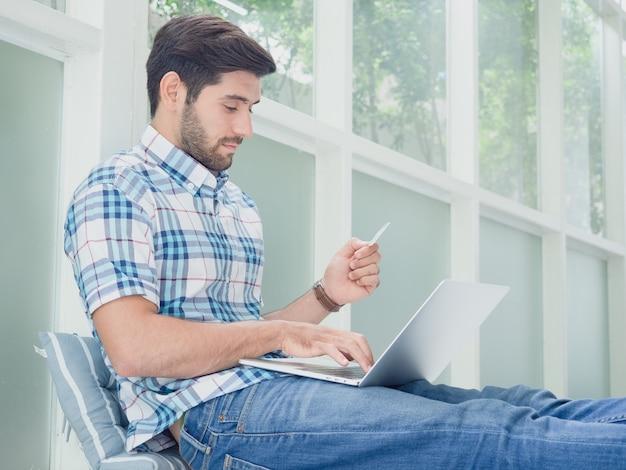 Jonge mens die online met creditcard thuis winkelt