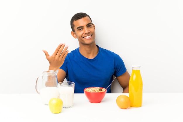 Jonge mens die ontbijt in een lijst heeft die uitnodigt te komen