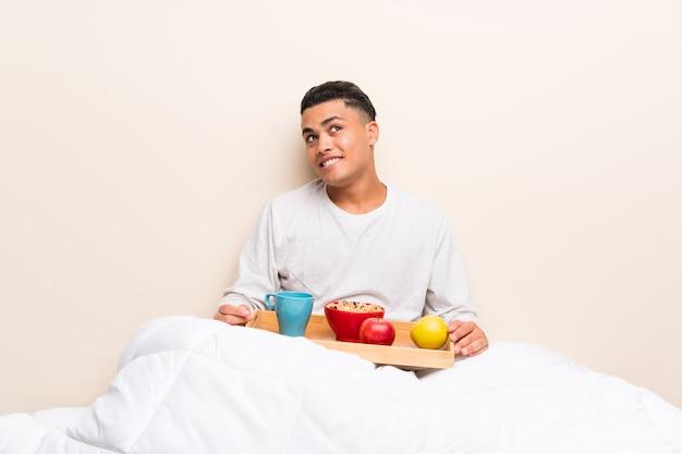 Jonge mens die ontbijt in en bed heeft dat omhoog lacht kijkt
