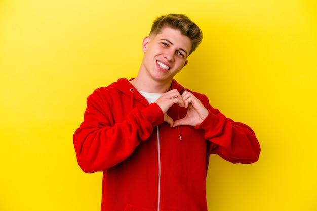 Jonge mens die op gele muur wordt geïsoleerd die en een hartvorm met handen glimlacht toont
