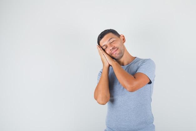 Jonge mens die op handpalmen leunt als hoofdkussen in grijs t-shirt en gelukkig kijkt