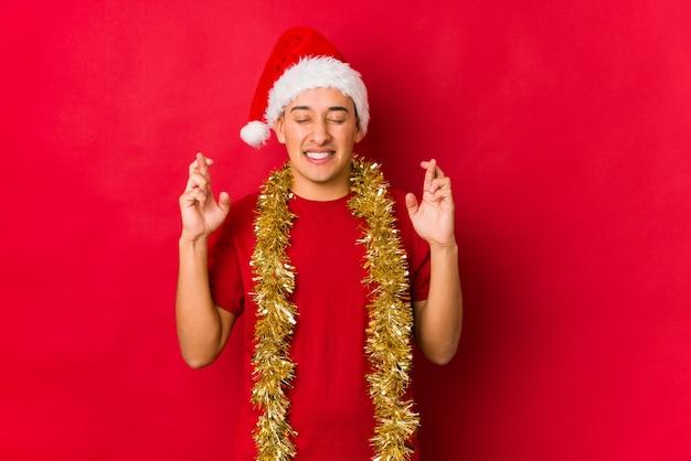 Jonge mens die op kerstmisdag vingers kruisen voor het hebben van geluk