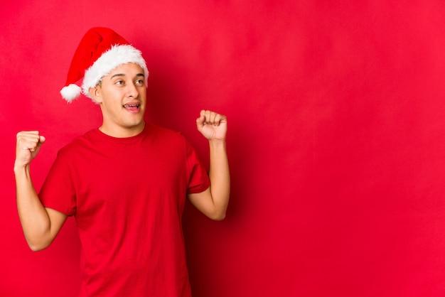 Jonge mens die op kerstmisdag vuist na een overwinning opheffen, winnaarconcept.