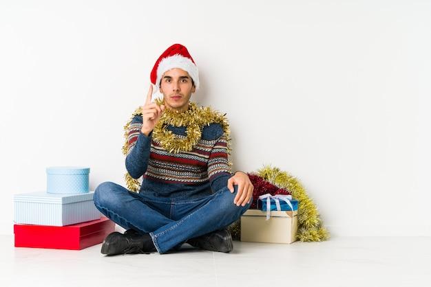 Jonge mens die op kerstmisdag zijdelings met twijfelachtige en sceptische uitdrukking kijkt.