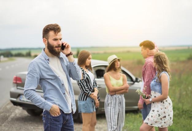 Jonge mens die op mobiele telefoon spreekt die zich voor vrienden bij wegreis bevindt
