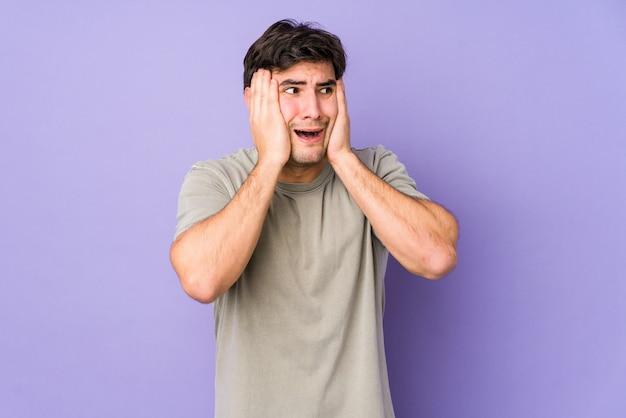 Jonge mens die op purpere behandelende oren wordt geïsoleerd met handen die niet te hard geluid proberen te horen.
