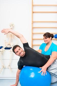 Jonge mens die op zwitserse bal in fysiotherapie uitoefent