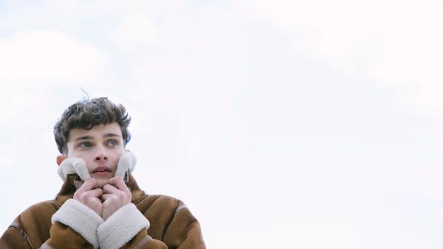 Jonge mens die oren behandelt met jasje met exemplaar-ruimte
