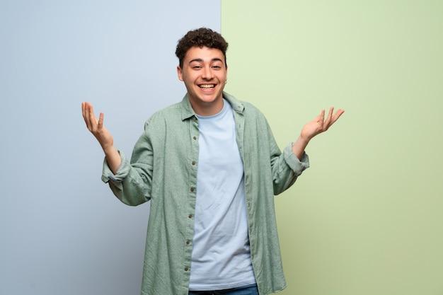 Jonge mens die over blauwe en groene muur met een zoete uitdrukking glimlacht
